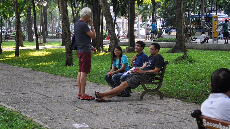 Students practicing their english with tourists in the shade, in 23/9 Park, Ho Chi Minh City