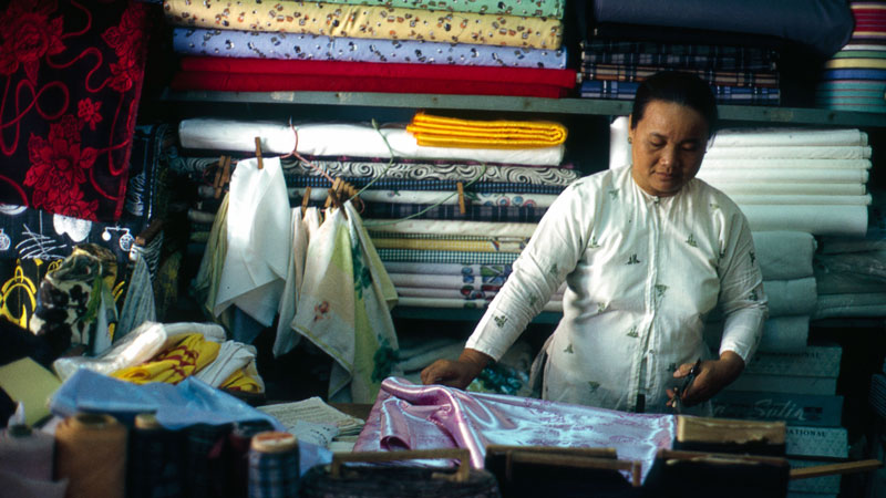 A woman measuring up silk for a tailored ao dai.
