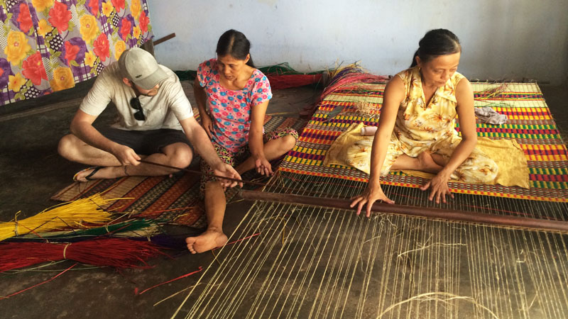 A tourist helping the locals weave a mat
