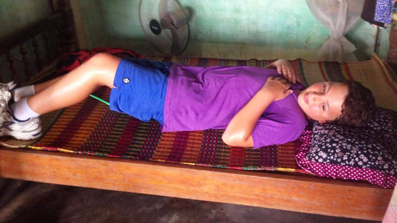 A tourist laying down a a traditional rush mat